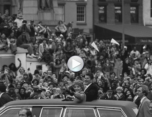 President Ronald Reagan and First Lady Nancy Reagan are in a black limousine and are standing up in the car to wave through the open roof to the crowds assembled along the Inaugural Parade route. January 20, 1981. Smithsonian Institution Archives, Record Unit 95, Box 59A, Folder: 11. Neg. no. SIA2009-0251.