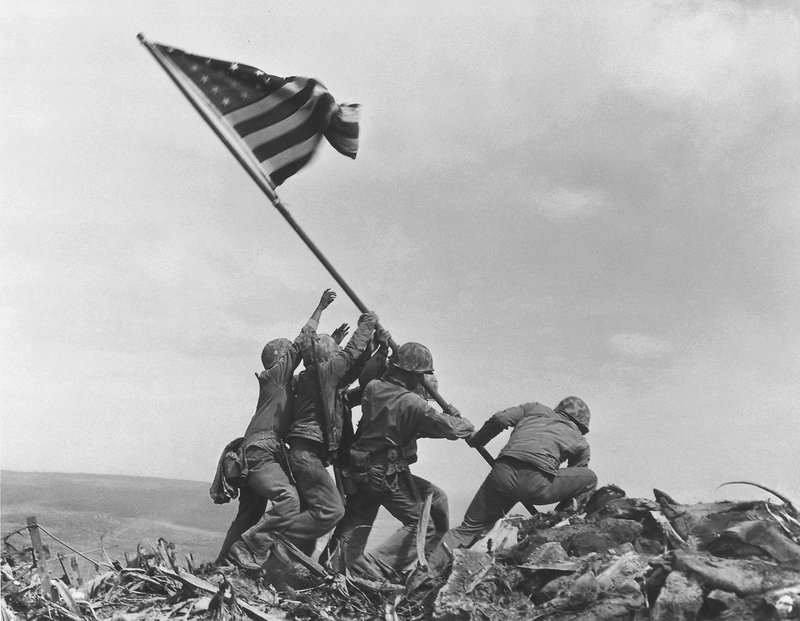 U.S. service members raise the American flag atop Mt. Suribachi in Iwo Jima, Japan, on Feb. 23, 1945