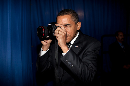 President Barack Obama takes aim with a photographer's camera backstage prior to remarks about provi