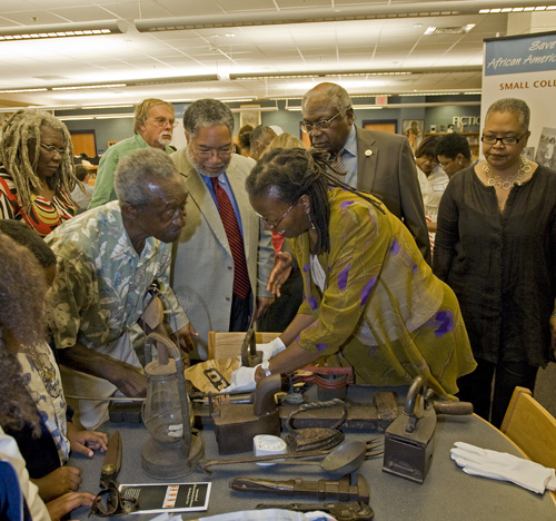 "Participants in the ""Save Our African American Treasures"" program held in May 2009 in Charleston, SC. Treasures is a national outreach program presented by the National Museum of African American History and Culture. Looking on (center rear) are NMAAHC Director Lonnie Bunch and Congressman James Clyburn (DSC), Photo by Michael Barnes."