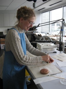 Intern Michal Long works to mend pages of the book with Tengujo paper and adhesive, Courtesy of Ricardo Penuela-Pava.