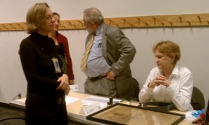 Sarah Stauderman of the Smithsonian Institution Archives, David Haberstich of the National Museum of American History's Archives Center, and Linda Edquist of the National Postal Museum consult with a visitor about her 1865 newspaper announcing Lincoln's assassination.