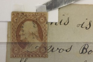 A detail of how a stamp was hinged back in its original location rather than pasted on as in the original assembly, so as to allow reading of text beneath the attachment, Courtesy Nora Lockshin and Anacostia Community Museum.