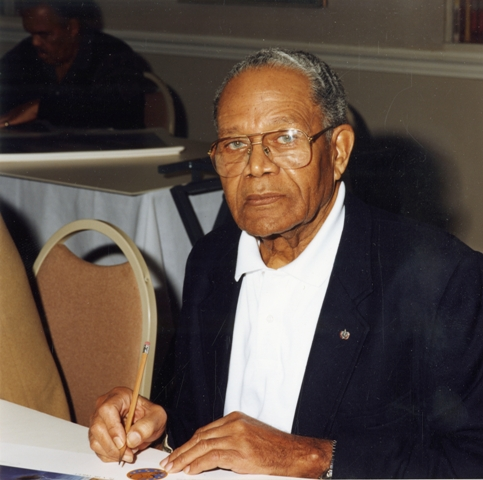 Louis R. Purnell sitting at a table, c. 1993, by Unidentified photographer, Color print, Smithsonian