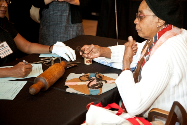 A participant discusses a lock of hair from a member of her family with NMAAHC staff at a Save Our A