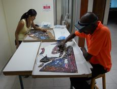 Conservation assistants Saori Kawasumi and Erntz Jeudy cleaning the painted surface.