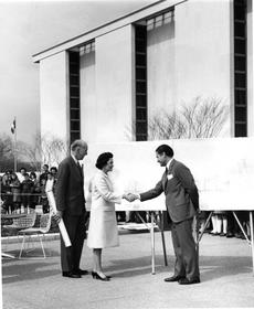 "Victor Lundy shaking hands with the First Lady, ""Lady Bird"" Johnson, with Secretary S. Dillon Ripley, as they review plans for Lundy's shade structures on the terrace of the new Museum of History and Technology, March 9, 1965.  Smithsonian Institution Archives. Neg. no. MAH-P65192-1."