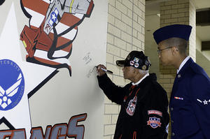 Captain  Claude R. Platte, Tuskegee Airman, signs a wall at the 323rd Training Squadron dedicated to the Tuskegee Airman, as his great nephew Airman Christopher Platte 331st Training Squadron looks on, December 11, 2009, by Michael Barnes.