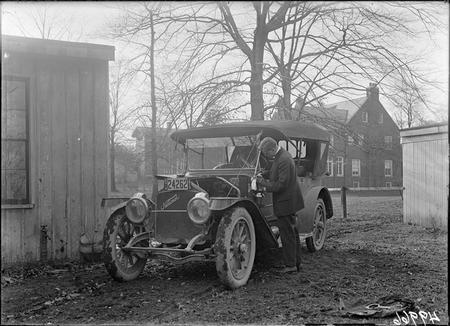 Unidentified man polishes kerosene oil side carriage lantern on an automobile.