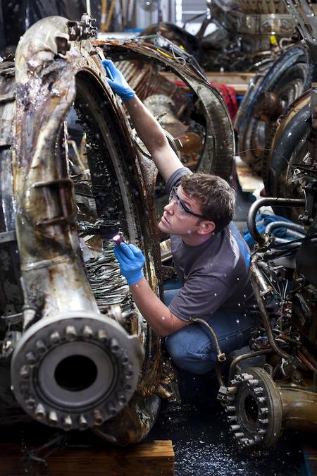 Jerrad Alexander, SpaceWorks Technician, examines an Apollo F-1 Thrust Chamber. By Gavin Peters.