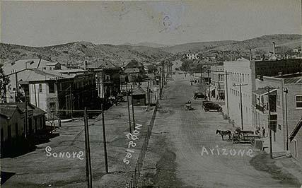 Reproduction of a photograph: Bird's-eye view of a street in the town of Nogales, which has the border running right through it. In the middle of the photograph is a wooden fence that is the dividing line, and to each side are city buildings, cars and carriages.