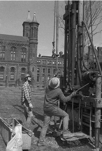 Two engineers from the Law Engineering Testing Company conduct a soil boring to obtain samples necessary to plans for the construction of the Quadrangle Building in the South Yard behind the Smithsonian Institution Building, 1979, by Richard K. Hofmesiter, black-and-white photographic print, Record Unit 371 - Office of Public Affairs, The Torch, 1955-1960, 1965-1988, Smithsonian Institution Archives, Neg. no. 79-3471-8.