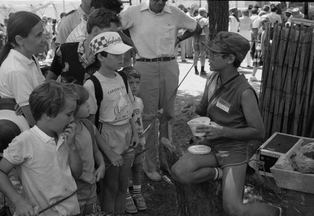Junior volunteer John McCauley demonstrates marblemaking to onlookers at the 20th Festival of American Folklife, in the Summer of 1986, by Dale Hrabak. Record Unit 371, Box 5, Smithsonian Institution Archives, Neg. no. 86-7301-15A.