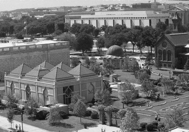 View of Arthur M. Sackler Gallery pavilion with pyramided roof located at the Smithsonian Institution in the four-acre Enid A. Haupt Garden, formerly known as the South Yard, 1987, by Jeff Tinsley, black-and-white photographic print, Record Unit 410 - Office of Public Affairs, Publicity Records, circa 1965-1974, 1987, Smithsonian Institution Archives, Neg. no. 87-7964-23.