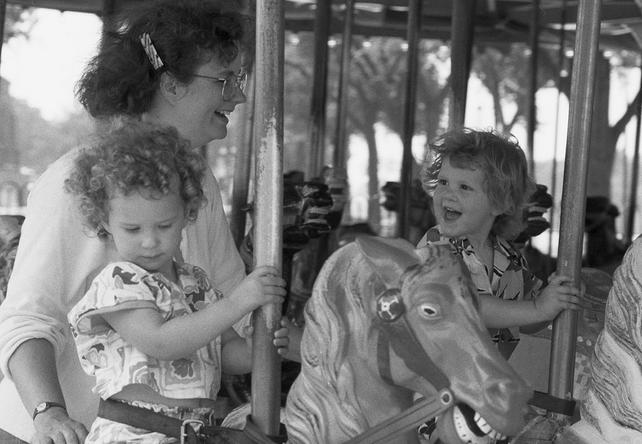 Young visitors ride the carousel outside Arts & Industries Building at the Smithsonian.  By Laurie Minor-Penland, 1988. Record Unit 371 - Office of Public Affairs, The Torch, 1955-1960, 1965-1988, Smithsonian Institution Archives, Neg. no. 88-11327-3.