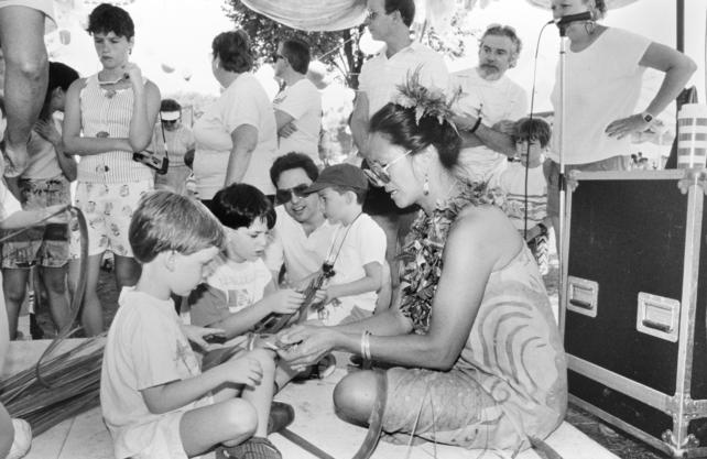 At the Festival of American Folklife in 1989, a participant from Hawaii demonstrates crafts to children while visitors look on, the making of an Hawaiian lei. Record Unit 95, Box 59A, Folder 14, Smithsonian Institution Archives, Neg. no. 89-18479.