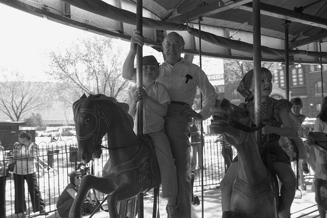 S. Dillon Ripley, eighth Secretary of the Smithsonian Institution, and unidentified children riding on the carousel in front of the Arts and Industries Building, 1977. Accession 97-003 - Office of Public Affairs, Photographs, 1965-1984, Smithsonian Institution Archives, Neg. no. 77-4394-24A.