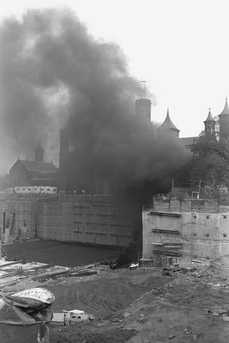 On October 15, 1984 (c. 8:30 a.m.), a thick, black smoke surrounded the Smithsonian Institution Building. It was caused by a fire in a tar-melting machine in the bottom of the Quad construction pit., 1984, by Mark Avino, black-and-white photographic print, Record Unit 371 - Office of Public Affairs, The Torch, 1955-1960, 1965-1988, Smithsonian Institution Archives, Neg. no. 84-11864-12A.