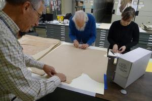 Volunteers Bob Demoyer (left), Jim Harle (center) apply skillful, reversible mends with guidance from Caitria Sunderland (right), so that they may stabilize the maps as needed. Image by Nora Lockshin, Smithsonian Institution Archives.