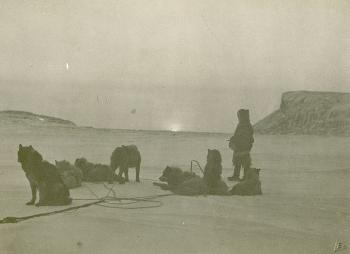 """Sunrise after a long winter.""  A man and his dogs gaze at the sun seen by the Rasmussen expedition for the first time after the winter. Photograph taken on Kent Peninsula, on Dease Strait, Northwest Territories, Canada, by Lee Hansen, photographer of Knud Rasmussen expeditions. Image # 2005-8640"
