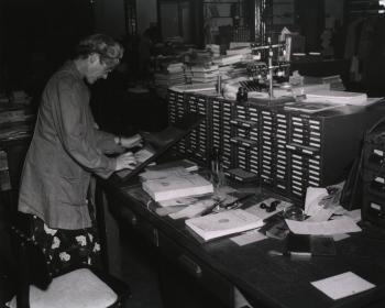 Edith E. Spaeth checking-in a serial using the kardex next to a card catalog, April 1948, National Library of Medicine, neg. no. A016976.