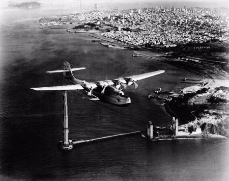 The China Clipper flies past the unfinished Golden Gate Bridge and heads toward Hawaii, November 22,