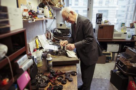 Paul Schweitzer repairing a typewriter, by Andrew White.