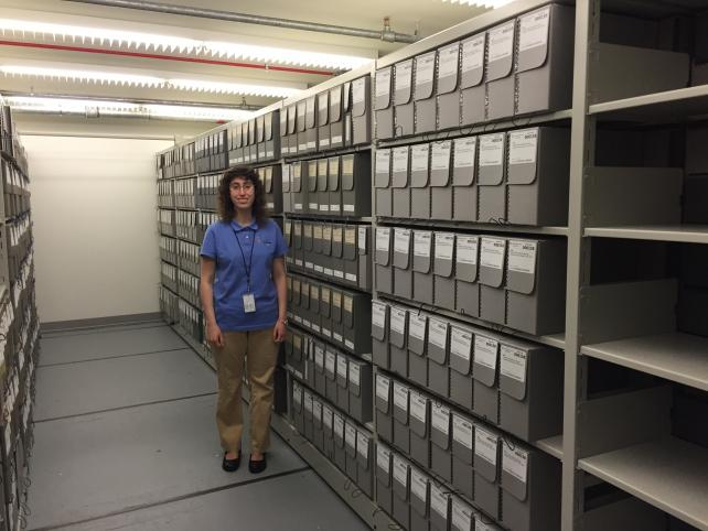 Heather in our collections storage space, alongside the collections she has helped rehouse.