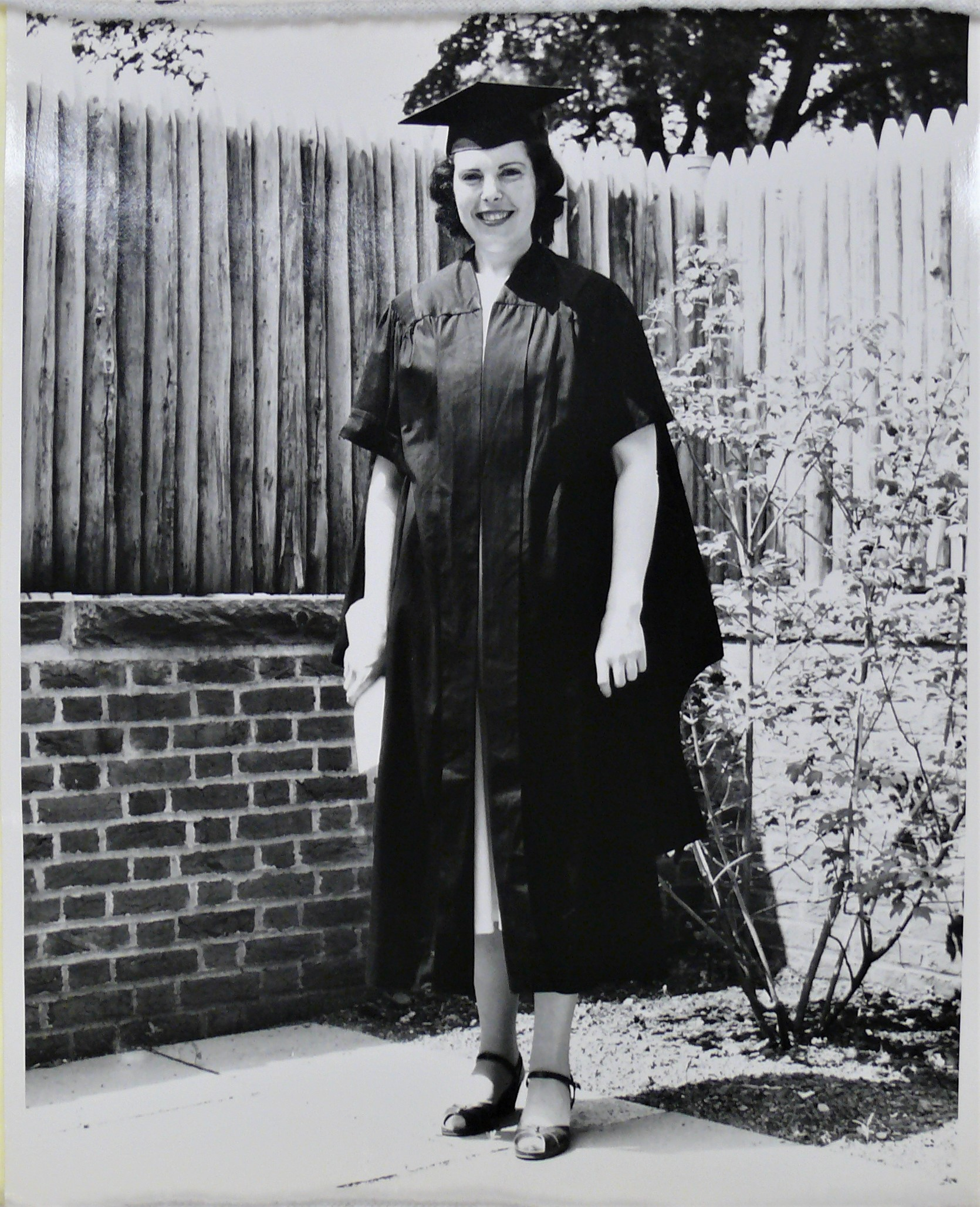 Black and white photograph of Crimilda standing in a graduation cap and gown.