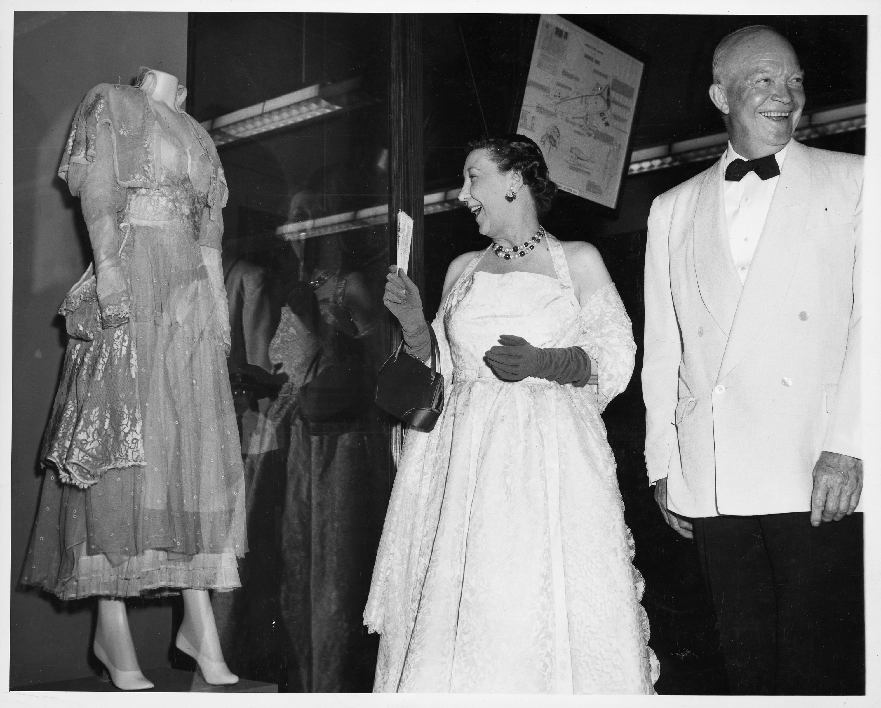 The Eisenhowers stand in front of a gown on exhibit. Both are smiling broadly.