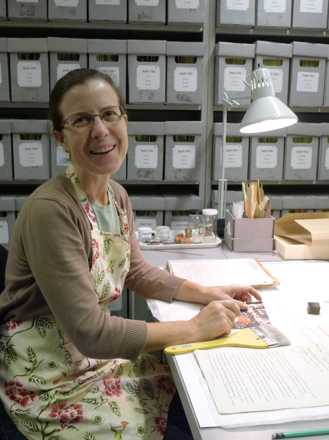 A person sits at a desk and smiles. Manuscript boxes are in the background.