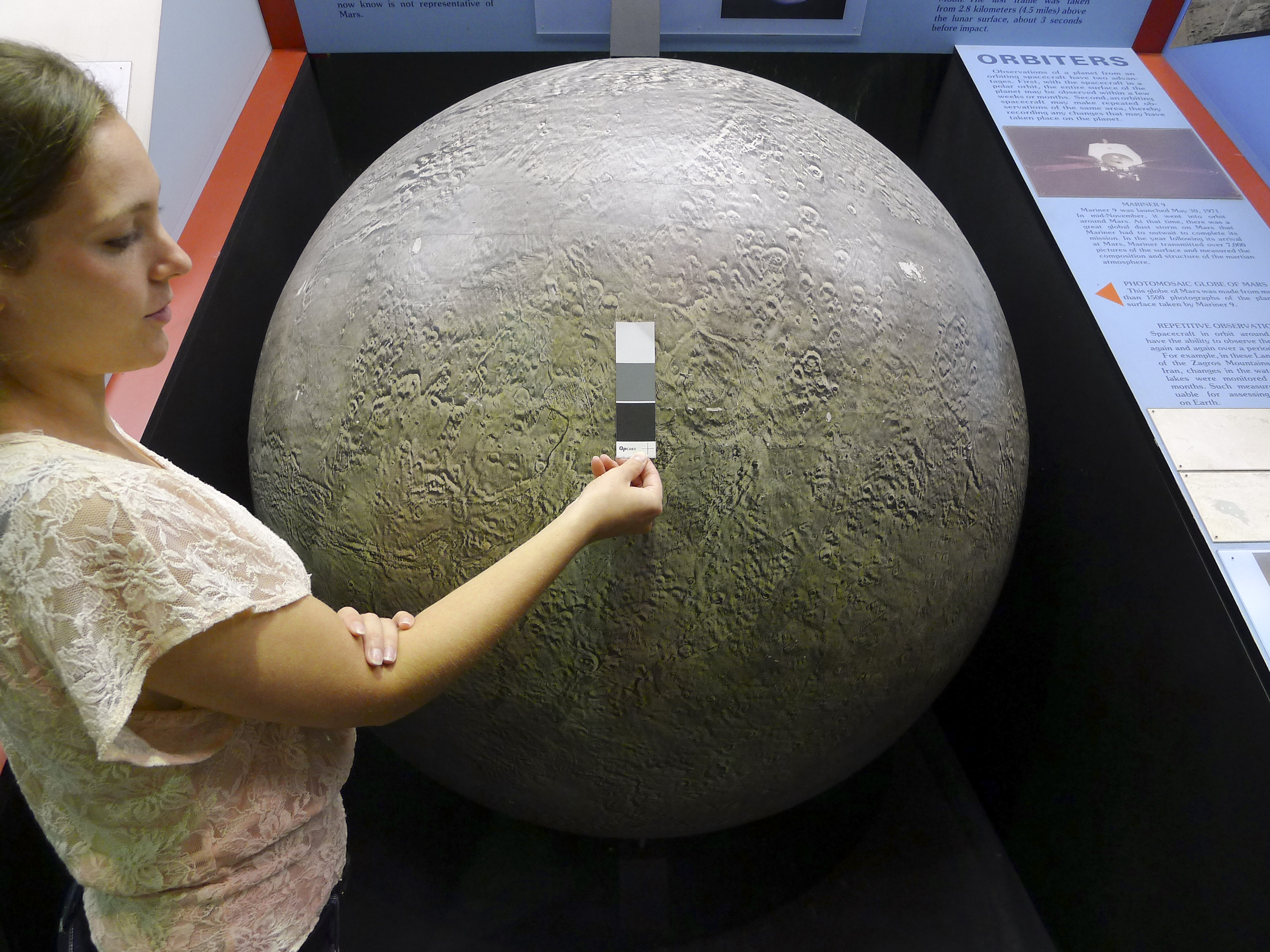 A person holds up a paint sample marker to a large, circular object.