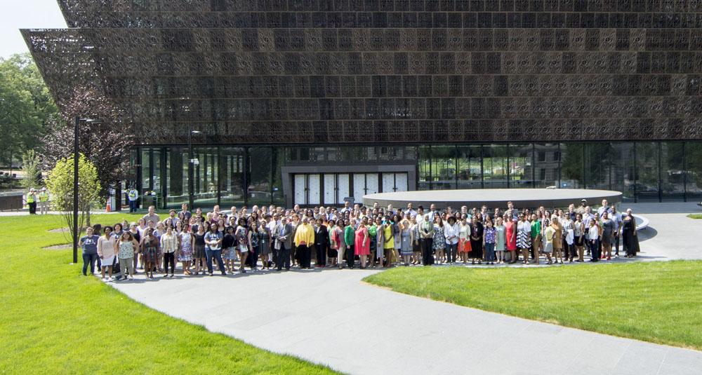 Group of people standing in front of metal-clad museum.