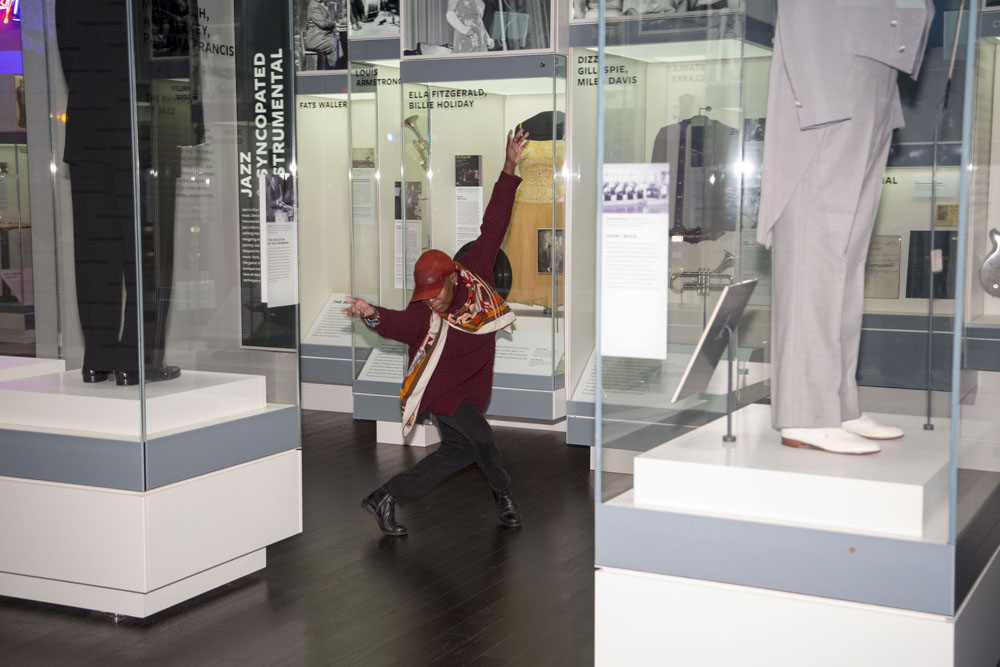 A dancer bowing between exhibition cases.