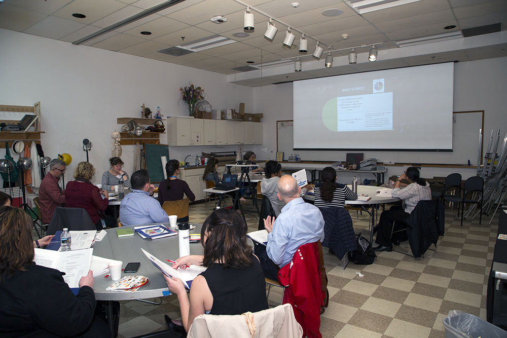 Staff seated at tables looking at screen with projection