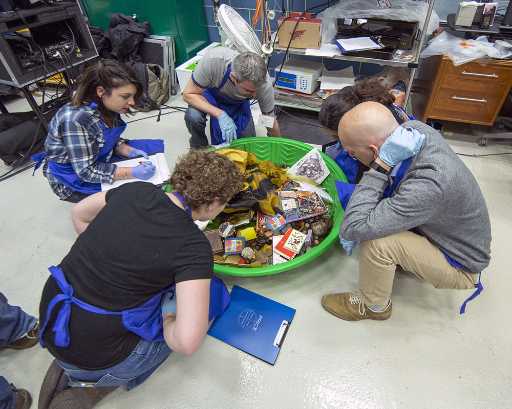 5 participants in blue aprons examine assorted objects collected in plastic child's pool