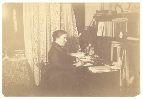 A woman, Alice Cunningham Fletcher, sits at her desk writing.