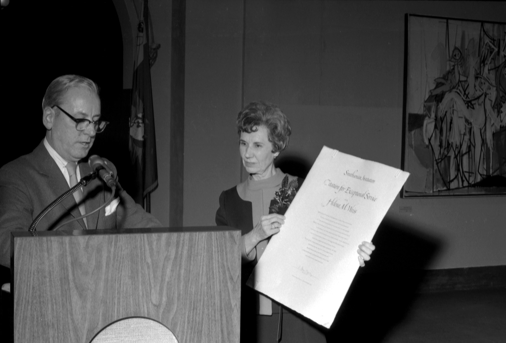 Helena Weiss stands at left holding a large award certificate for the Secretary's Gold Medal for Exc