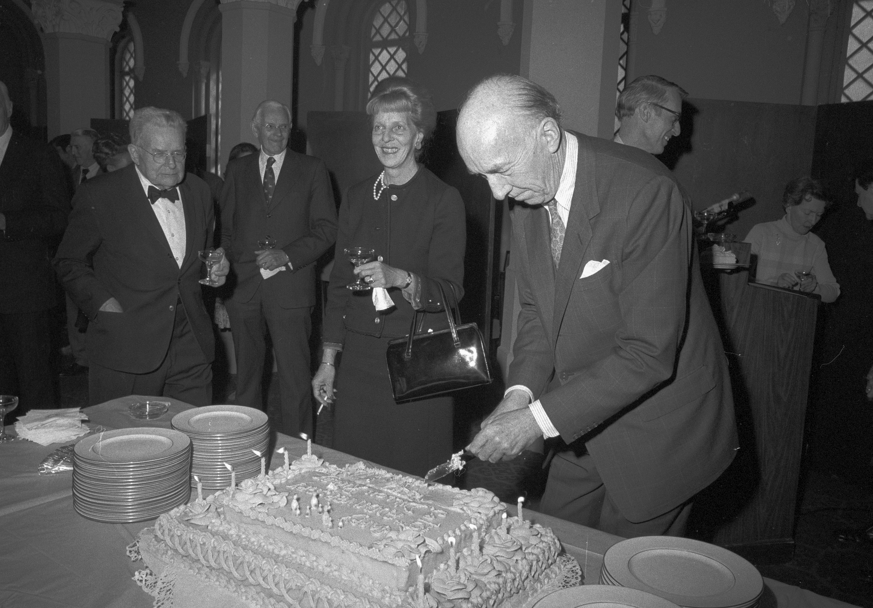 Person standing and cutting a large cake.