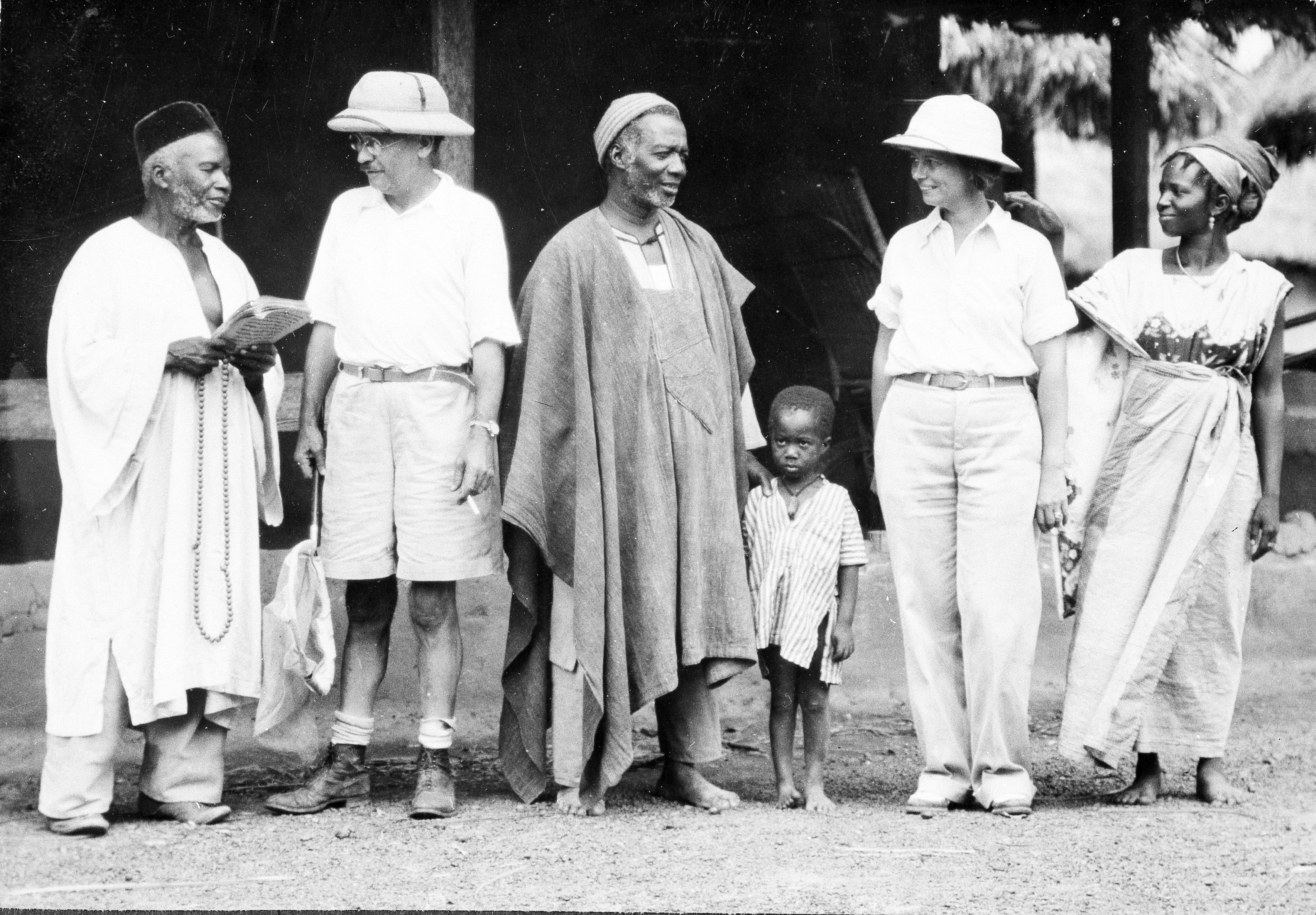 William and Lucile Mann stand with people from a village they are visiting.