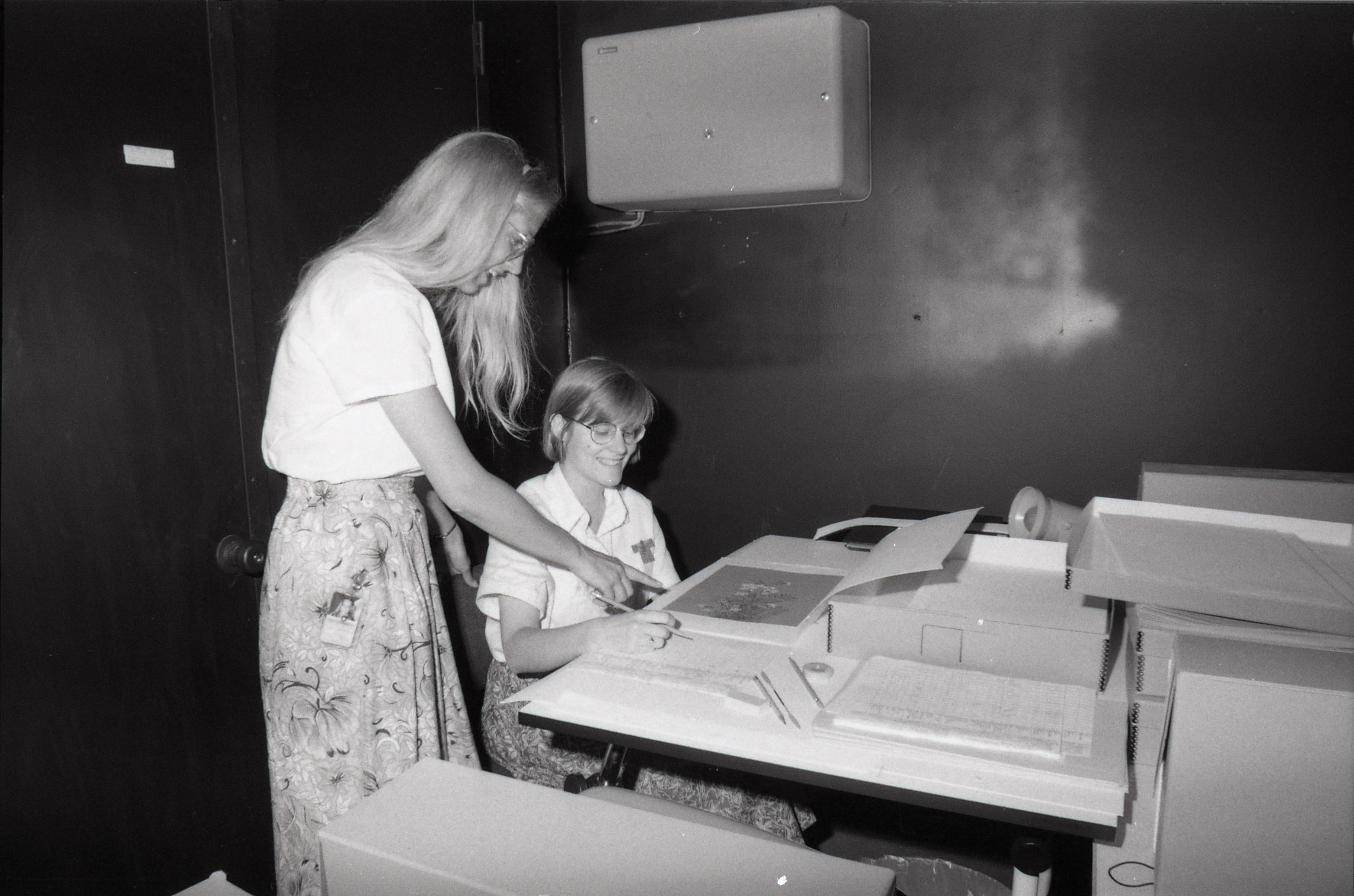 Black and white image of two persons examining archival material.