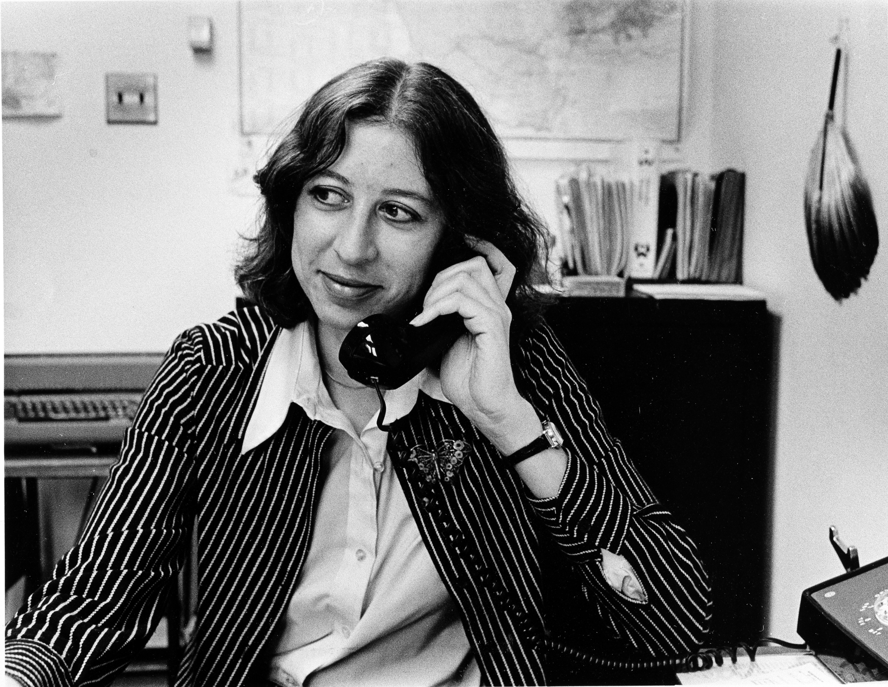 Black and white image of person seated and speaking on phone.