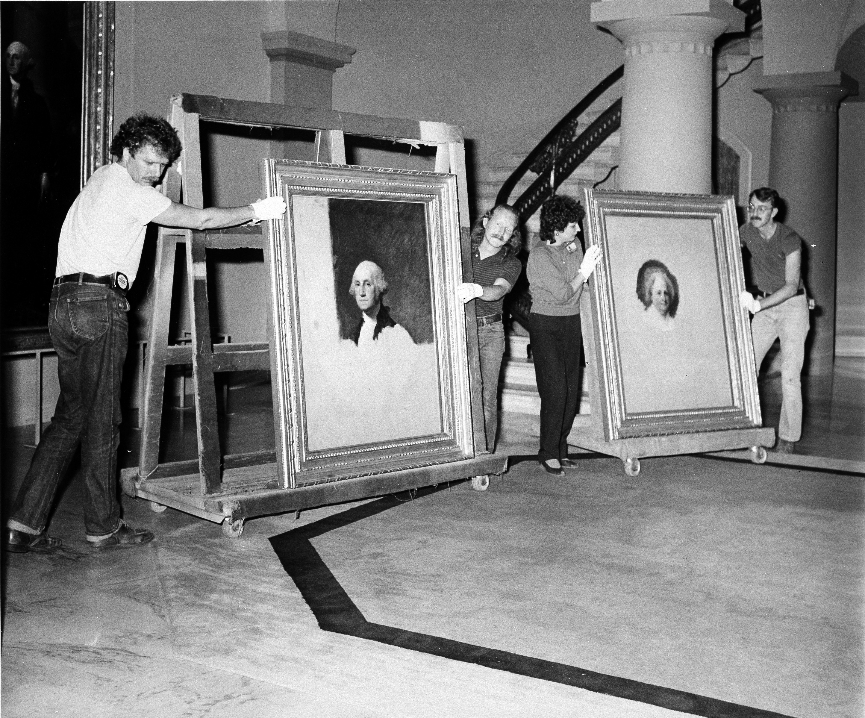 Four people work on moving the Stuart portraits.
