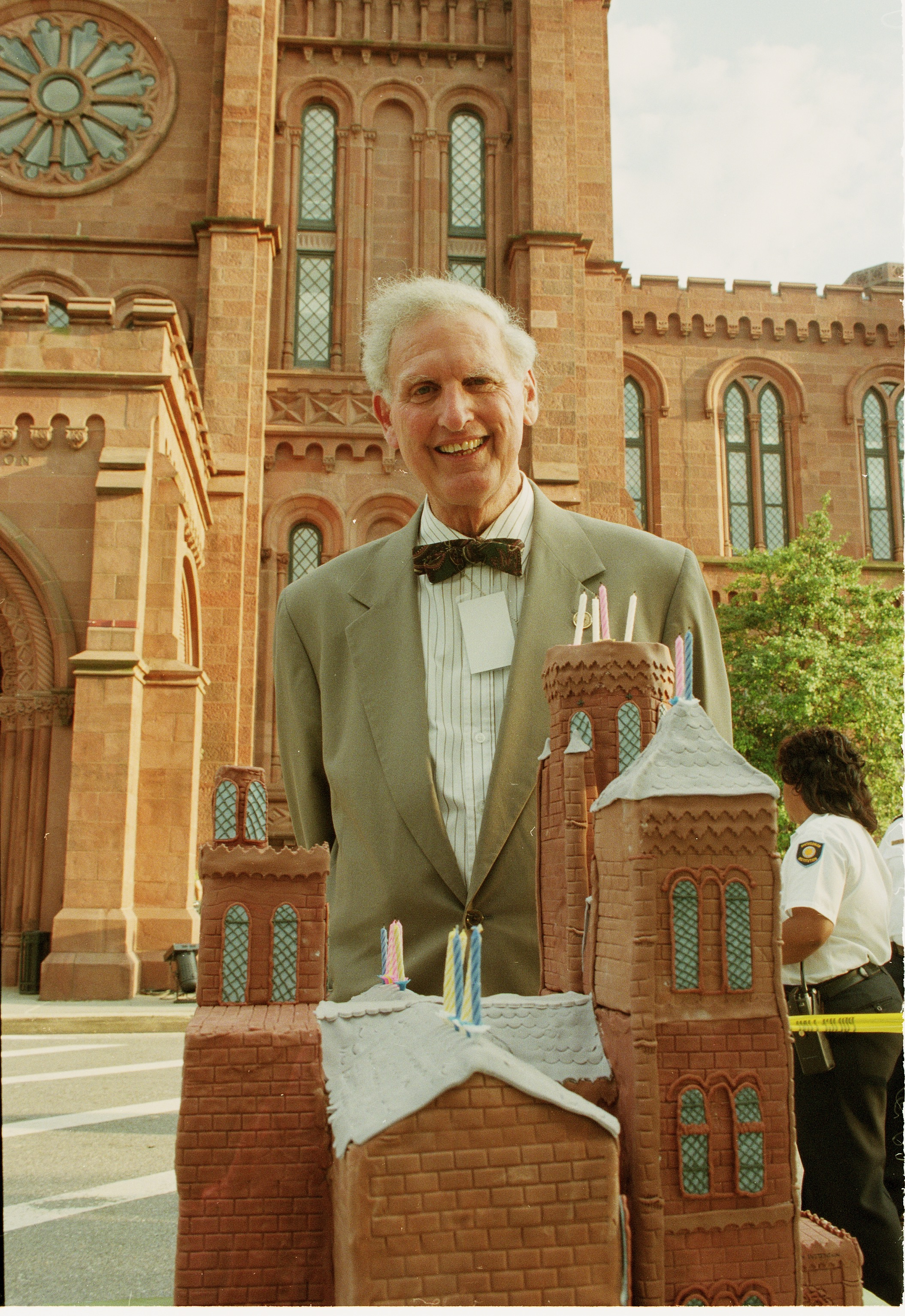 Person in bow tie standing behind a cake built like a building.