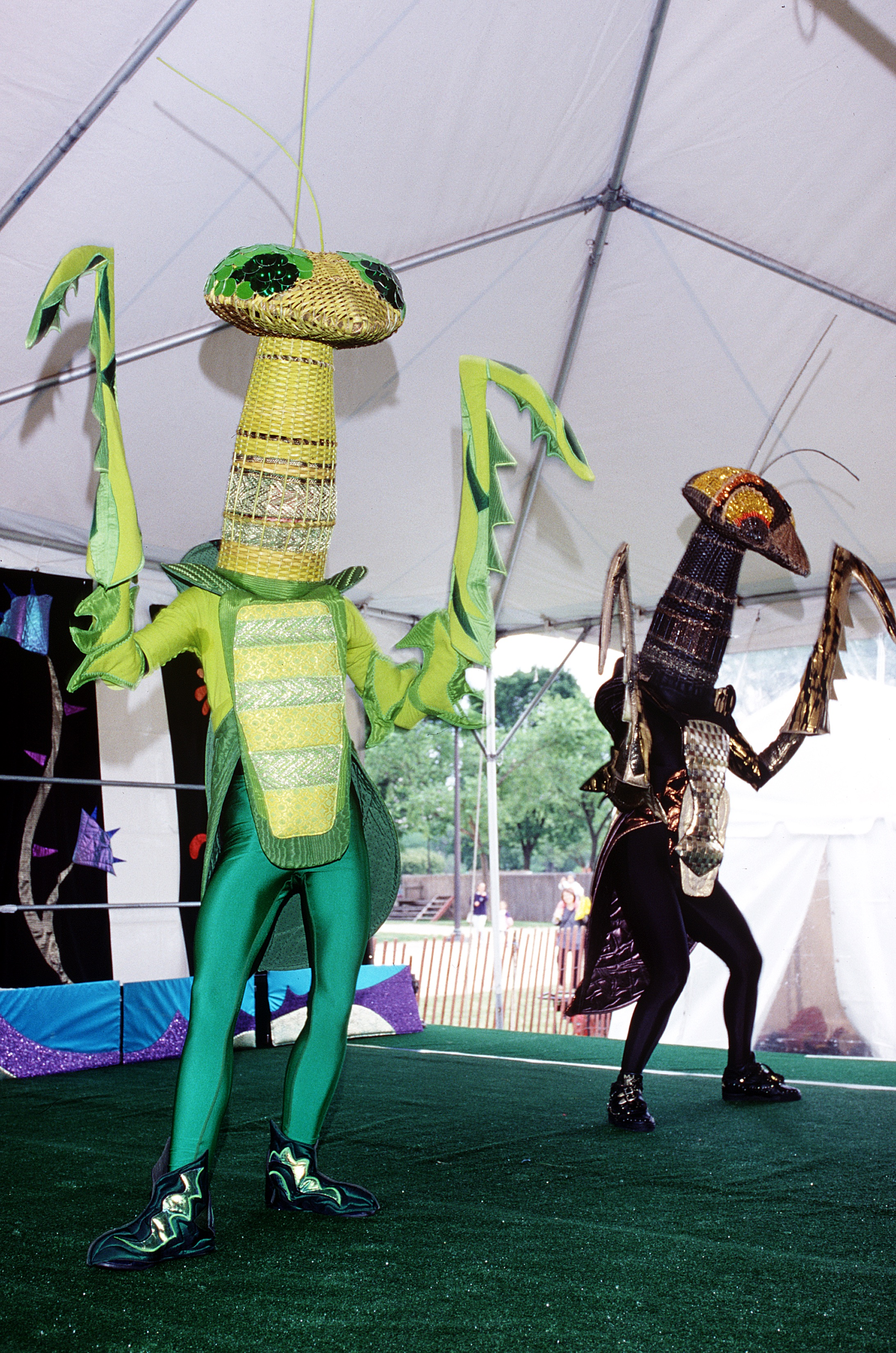 Two people in praying mantes costumes perform on stage.