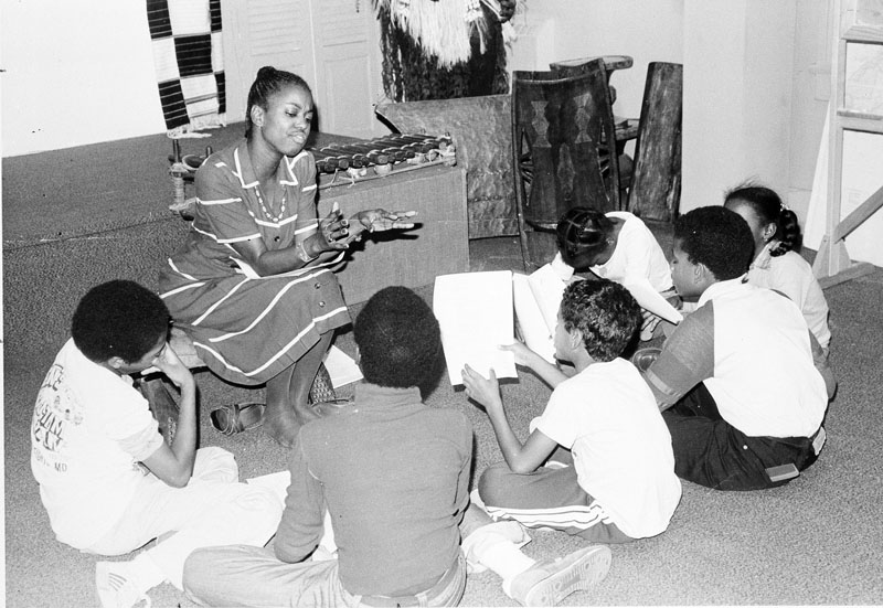 Six children, visiting the National Museum of African Art, listen to Amina Dickerson, program director, at the museum. Smithsonian Institution Archives Record Unit 371, Box 2, Folder November 1978.