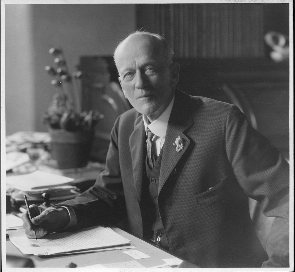 Charles Doolittle Walcott (1850-1927), fourth Secretary of the Smithsonian Institution from 1907 to 1927.  Walcott is seated at his desk writing. Smithsonian Institution Archives, Record Unit 95, Box 23, Folder 23.