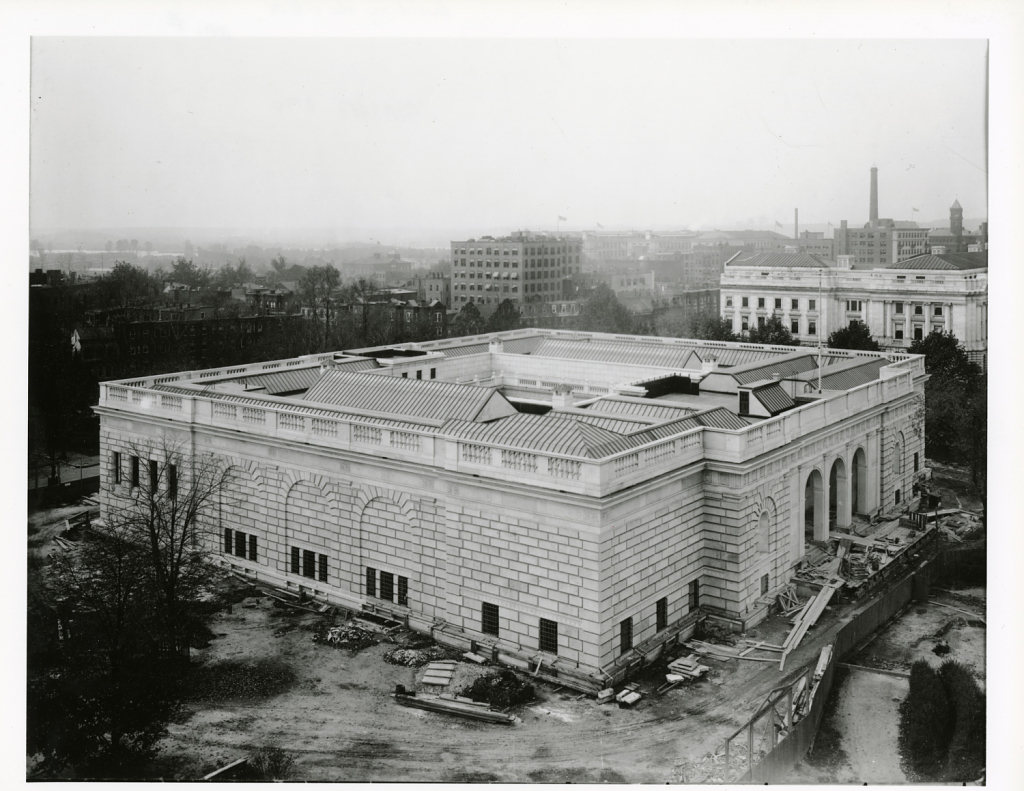 An aerial view of the north and east sides fronts of the Freer Gallery of Art shows construction debris on the ground.  Smithsonian Institution Archives, Collection 02-082, Box 2, Folder Photographs, Exterior - North Front.