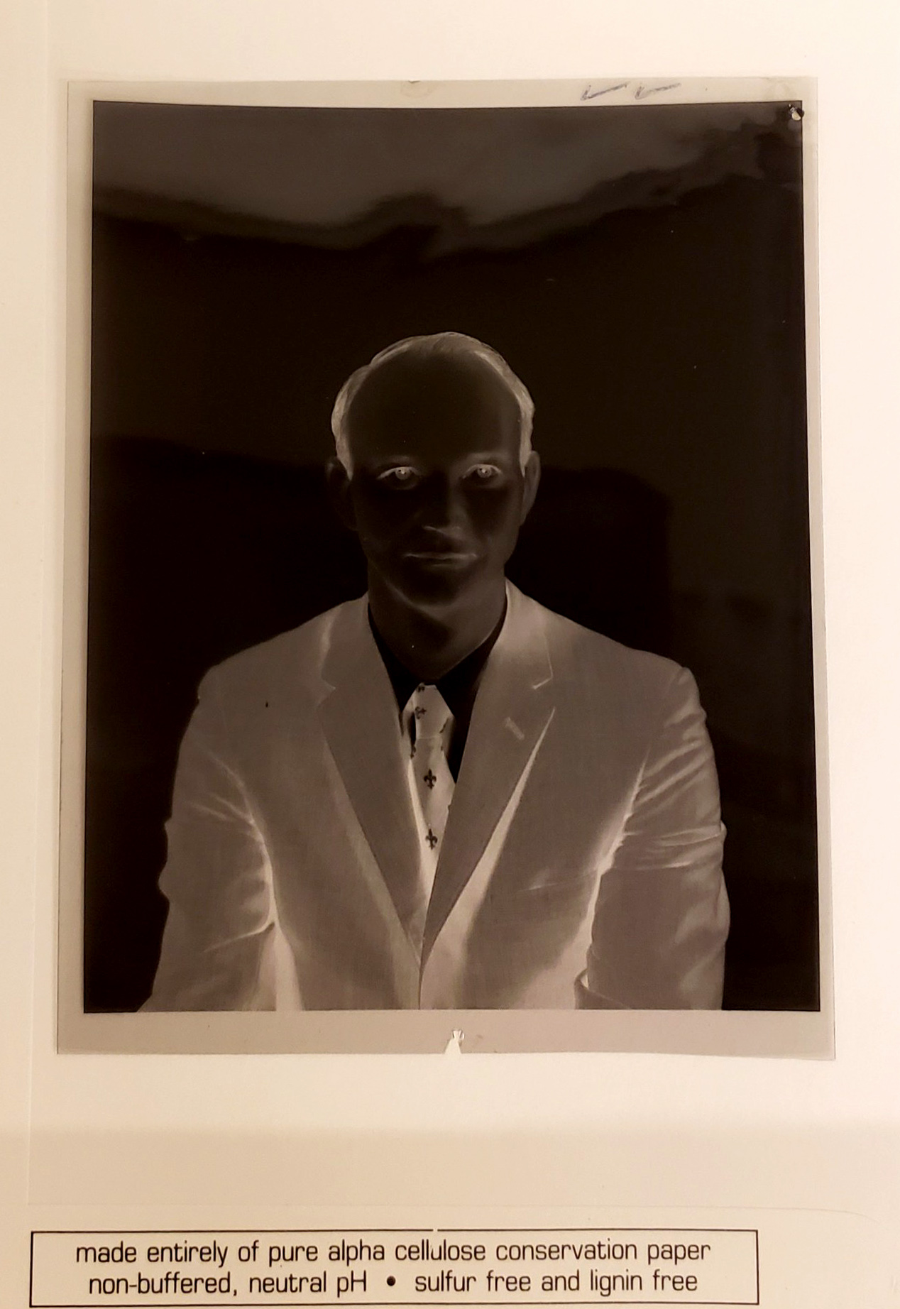 Negative of a portrait of a man in a suit.