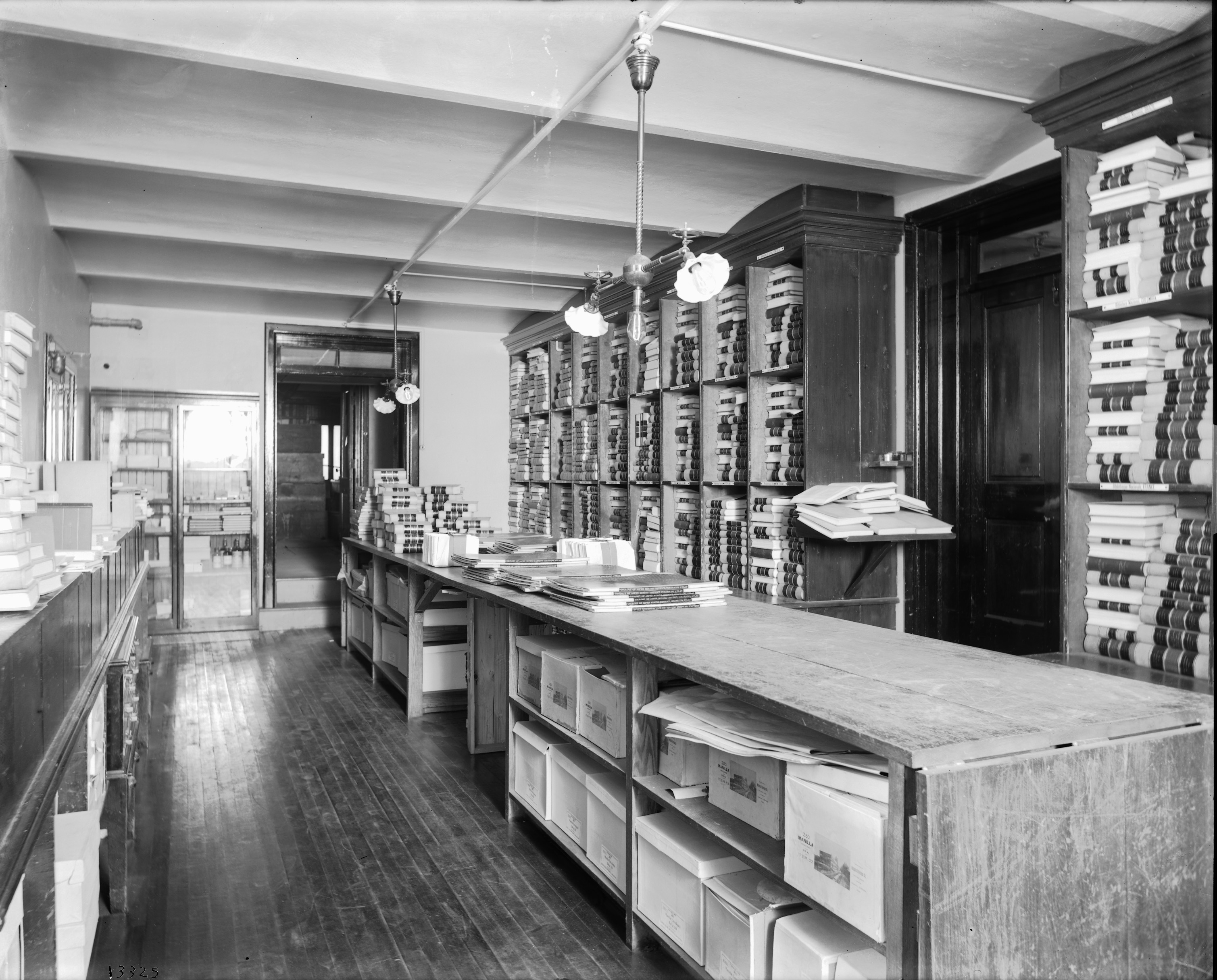 Black and white image of rows of shelves with boxes and books.